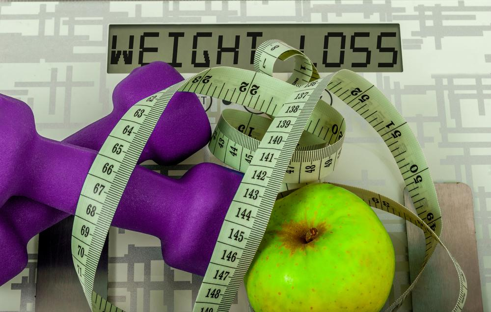 Dumbbells, apple, and measuring tape on scale