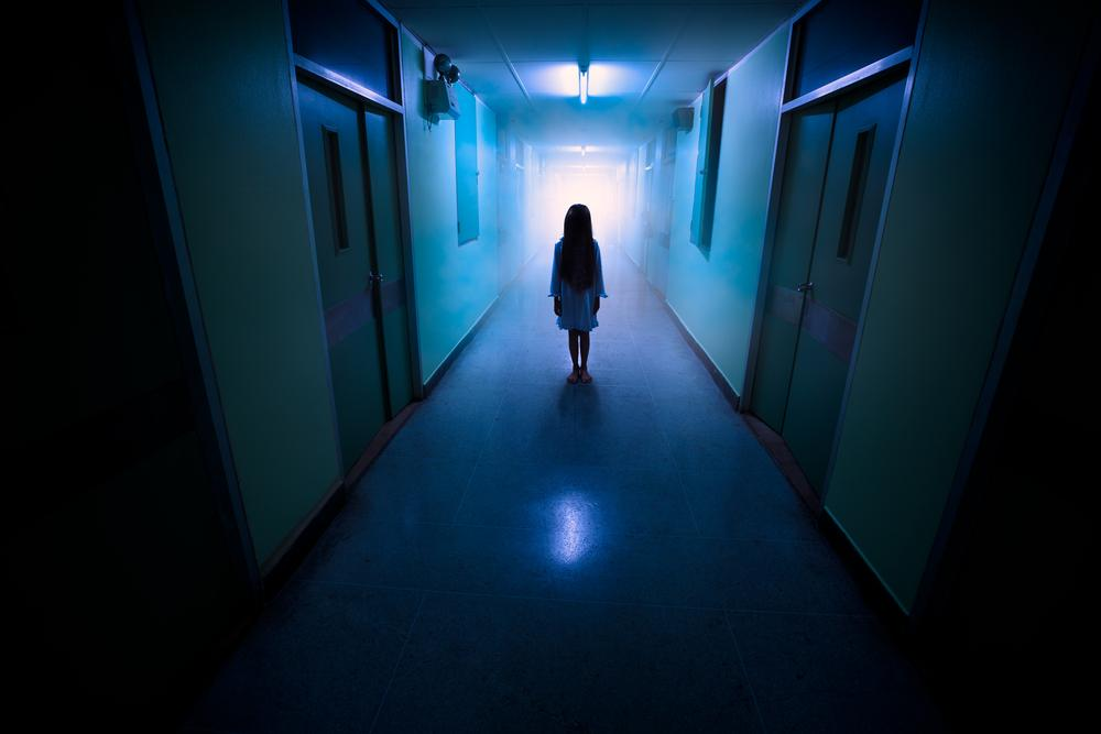 Little girl in empty and dark hallway