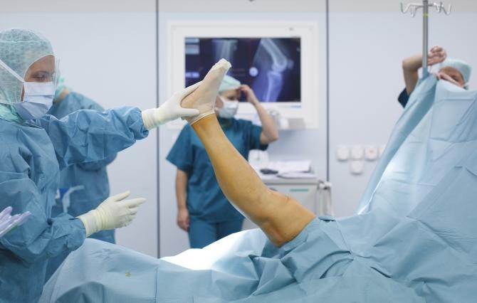 Doctors and medical staff work during knee prosthesis surgery
