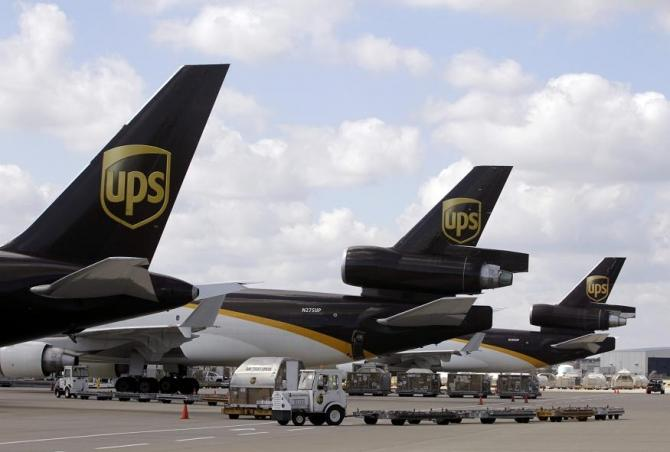 UPS employees load containers onto an aircraft at the World Port air hub during a visit by U.S. Treasury Secretary Timothy Geithner in Louisville, Kentucky September 26, 2011.