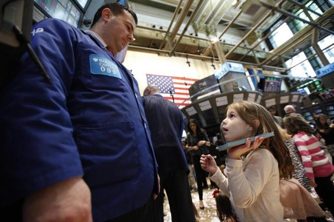Trader Mike Sciulli talks with his daughter on the floor of the New York Stock Exchange during the NYSE's annual kids day November 25, 2011.