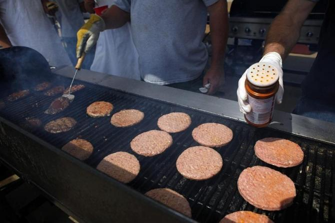 Volunteers cook hamburgers for tornado victims and workers in a supermarket parking lot in Joplin, Missouri May 27, 2011.