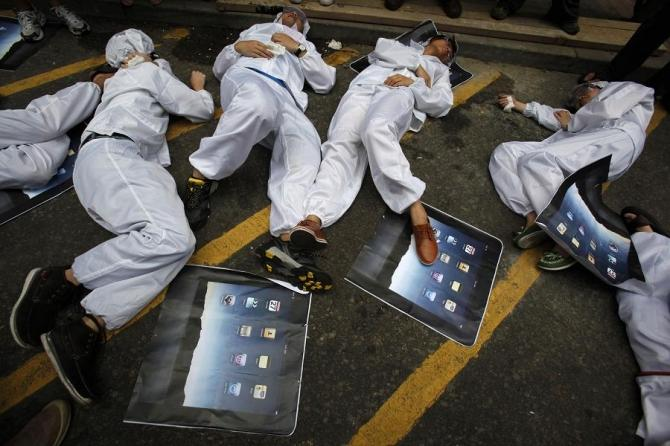 Local and mainland Chinese university students, in the role of Foxconn workers, lie on the floor as they act out being chemically poisoned during a street drama in Hong Kong May 7, 2011.