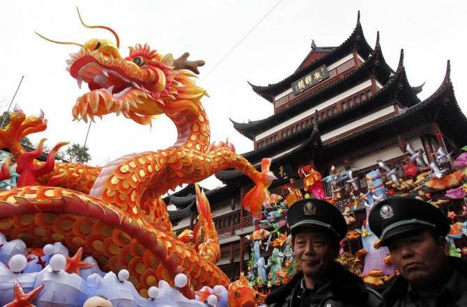 Security guards walk past a dragon lantern among other Chinese New Year decorations at Yuyuan Garden in downtown Shanghai January 17, 2012.