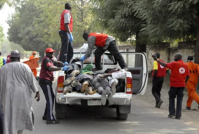 Red Cross officials load bodies into a truck