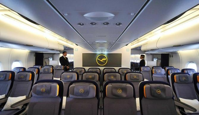 Flight attendants stand in aisle of the Economy Class in new Airbus A380 aircraft for Lufthansa.