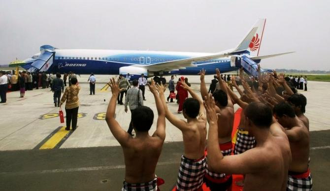 Indonesian dancers perform near a brand new Boeing 737-900 ER series in Jakarta.