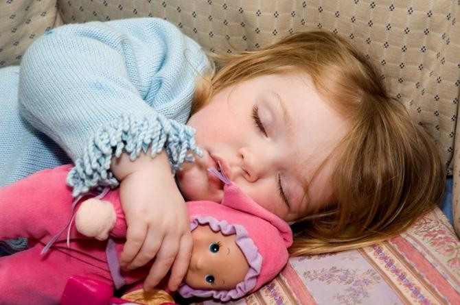 A girl asleep with her doll.