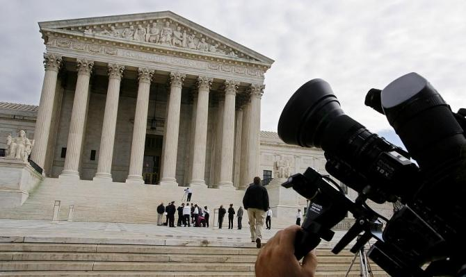 A television camera is pointed at the facade of the Supreme Court.