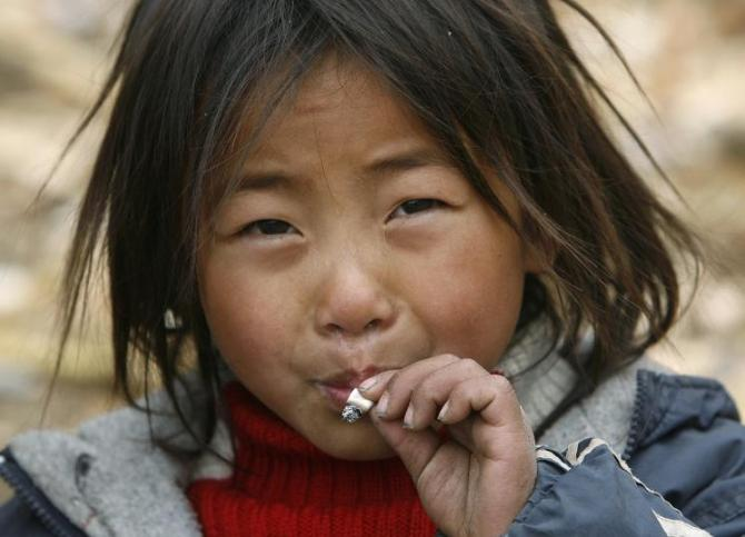 A child from the Yi ethnic minority smokes a cigarette at Dayingpan Village in Yuexi County, China.