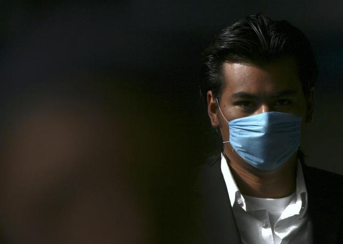 A man wears a surgical face mask as he walks to the Metro station in Mexico City April 27, 2009.