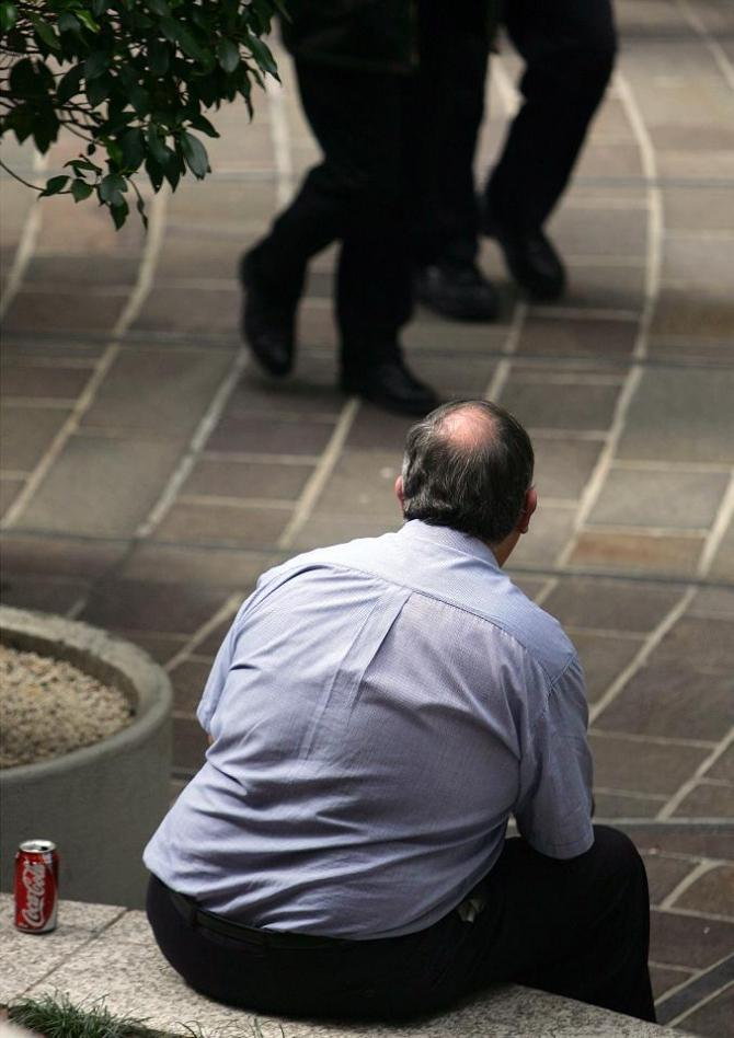A man rests at lunchtime at an outdoor cafe in Sydney September 6, 2005.