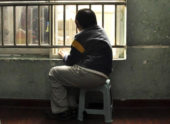 An autistic child looks out of the window at a school for autistic children in Tianjin municipality March 31, 2010.