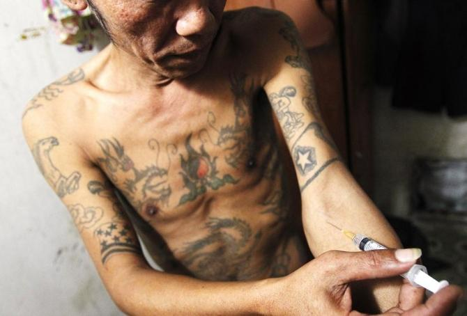 Tuan Anh Nguyen, 45, injects a syringe filled with heroin in his rented room in Hanoi November 23, 2011. Tuan Anh began abusing drugs 23 years ago after being released from prison. He has since spent most of his life in prisons and rehabilitation centres.