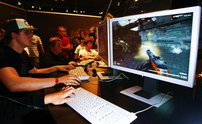 """Visitors play the game """"Karma"""" at an exhibition stand at the Games Convention Online 2009 fair in Leipzig"""