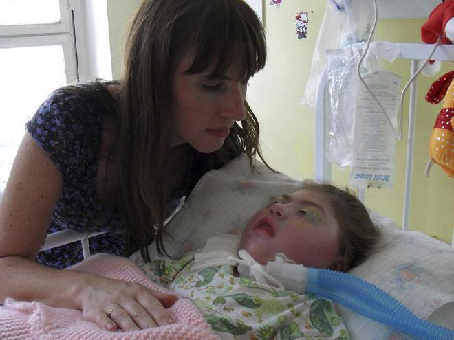 Silvia Herbon nurses her daughter, Camila, who has been in a coma since she was born three years ago and has no brain activity or other vital signs, in Buenos Aires.
