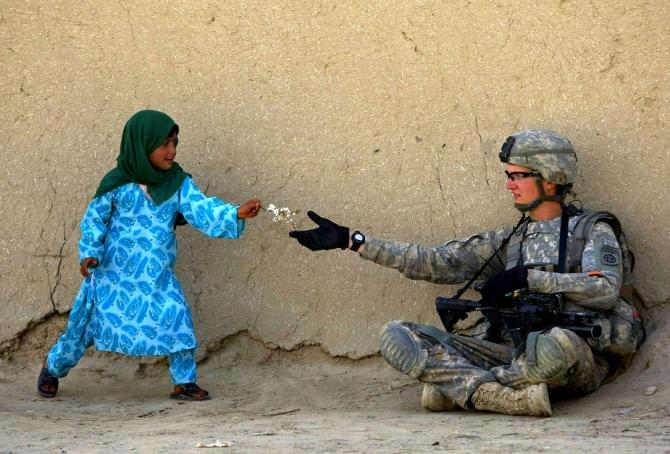 A U.S. soldier receive flowers from an Afghan girl during a patrol in the Arghandab valley in Kandahar province, southern Afghanistan