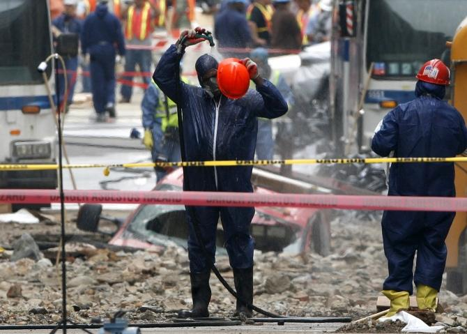 A worker wearing Hazmat suit cleans himself off with a hose at the site of a steam pipe explosion in New York