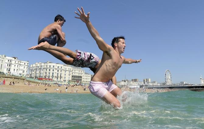 Youths jump into the sea in Brighton