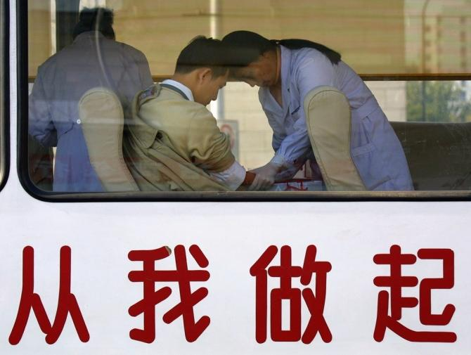 """A Chinese man donates blood at a government-run mobile donation centre decorated with Chinese characters which read """"Start From Me"""" in Beijing November 18, 2001."""