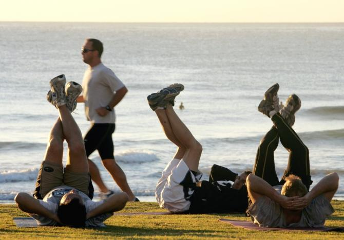 Jogger passes fitness enthusiasts performing stretching exercises after sunrise at Queenscliff Beach in Sydney