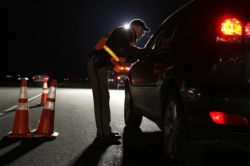 police asks a driver if he has been drinking while smelling for alcohol