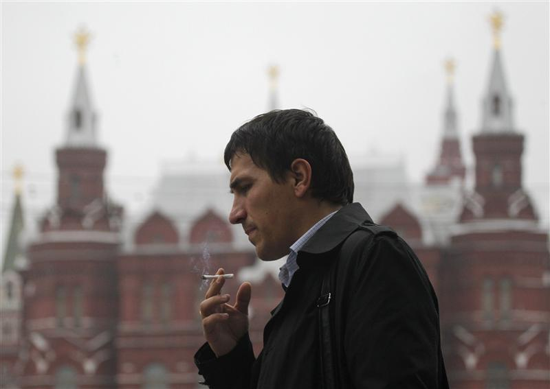 man smokes along a street in central Moscow