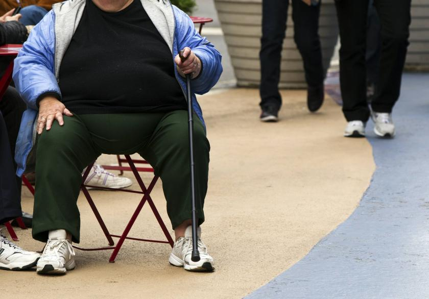 An overweight woman sits on a chair in Times Square