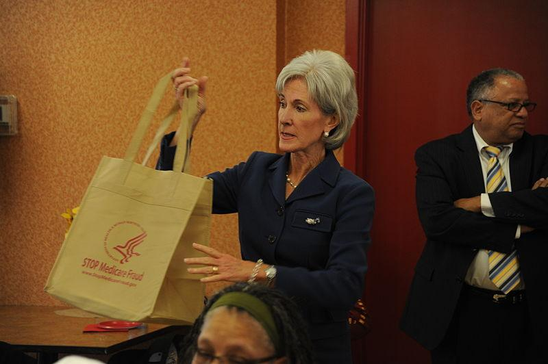 "Health Secretary Kathleen Sebelius holds up a ""Stop Medicare Fraud"" tote bag"