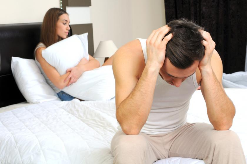 Upset man having problems with girlfriend in bedroom