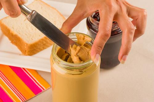 Woman about to spread peanut butter on sandwiches