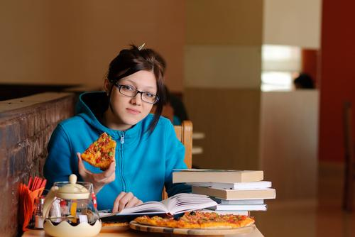 College student eating pizza and studying