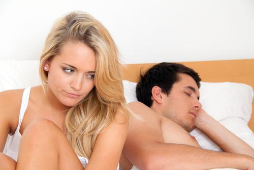 Woman sitting on bed upset while man is sleeping