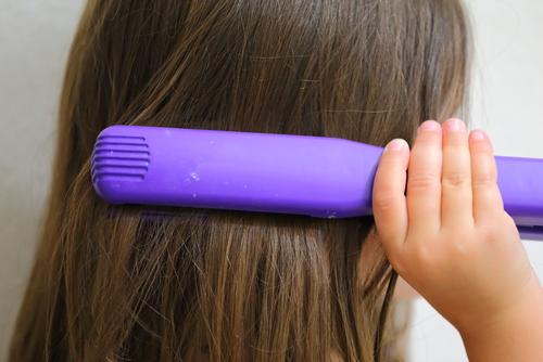 Young girl straightening her hair