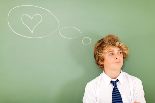 Boy thinking about love next to chalkboard