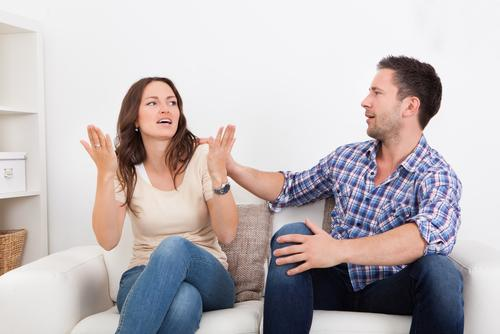 Frustrated couple on couch fighting with each other