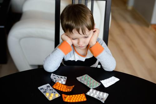 Depressed boy sitting in front of medications