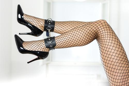Female legs with fishnet stockings in high heels tied to ankle cuffs
