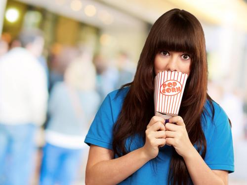 Girl covering mouth with empty popcorn packet outside