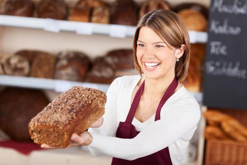 Bakery worker holding out a loaf of wholewheat
