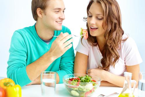 Man feeding woman vegetable salad