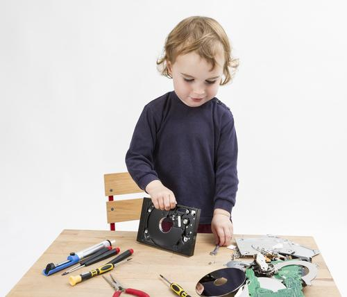 Preschooler with computer parts on wooden desk
