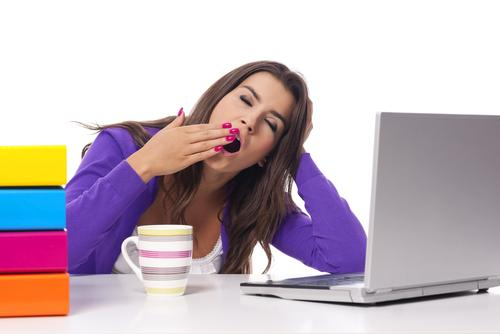 Woman yawning with coffee, books, and laptop on desk