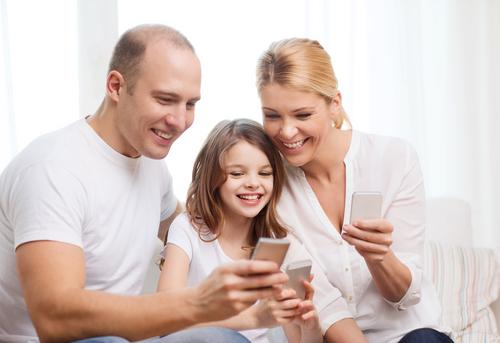 Smiling parents and child holding electronic devices in their hands