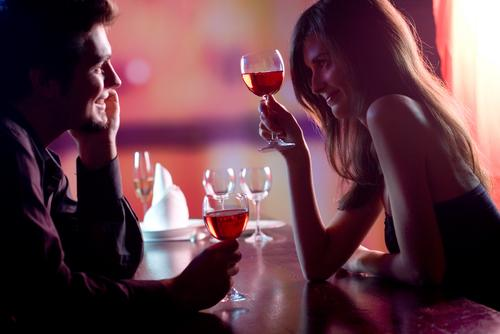 Young couple sharing a glass of wine in restaurant