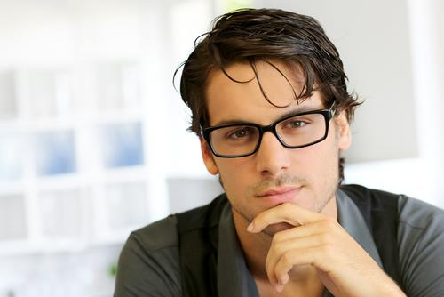 Man wearing glasses with hand under chin