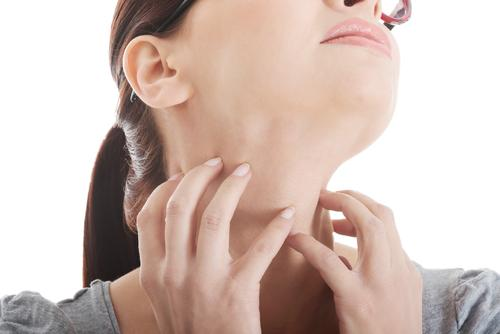 Woman scratching neck with fingernails