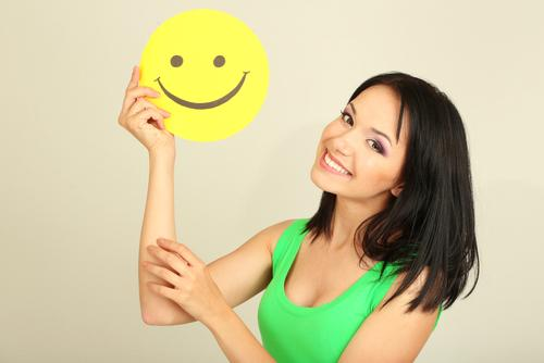 Woman smiling holding smiley face