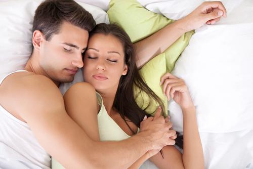 Couple holding hands and sleeping in bed