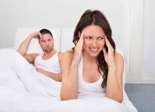 Woman frustrated sitting on bed in front of man